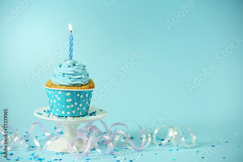 Obraz na plátne  Delicious cupcake on table on blue background