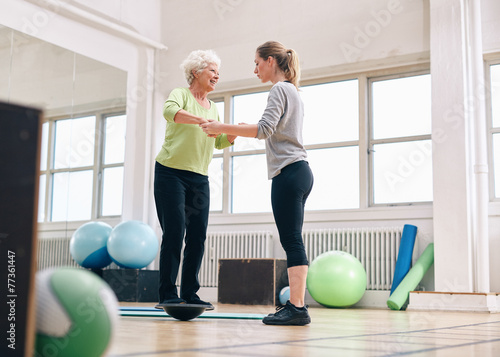 Canvas Print Trainer helping senior woman on bosu balance training platform