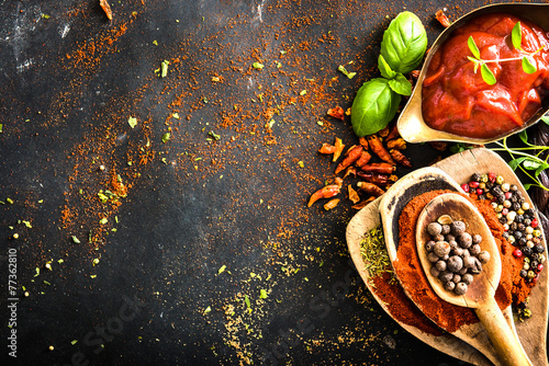 Wooden spoons with spices and tomato sauce