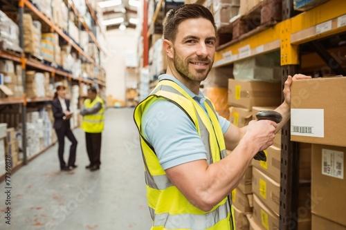 Obraz Warehouse worker scanning box while smiling at camera - fototapety do salonu