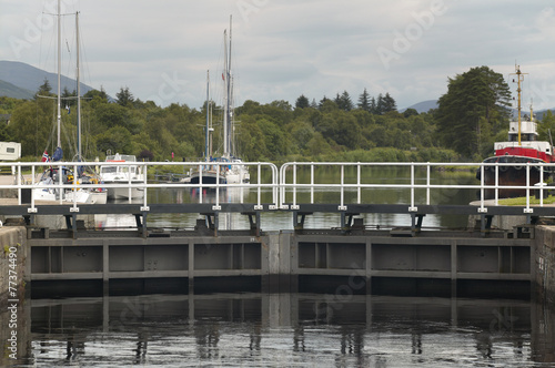 Fotografie, Obraz  Caledonian canal with sailboats and lock in Scotland