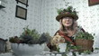 Grandma with plants in her hat and around her staring at camera