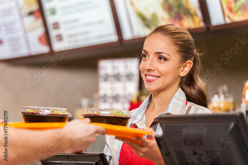 Restaurant worker serving two fast food meals with smile.