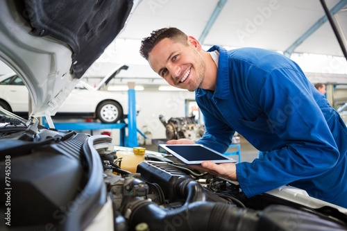 Mechanic using tablet on car