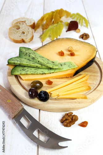 Staande foto Zuivelproducten Cheese platter: solid cheese, olives, walnuts and autumn leaves