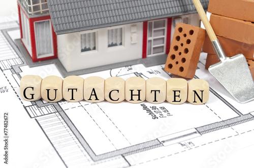 Foto  Bauplan mit Ziegelstein und Haus mit Gutachten
