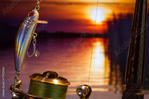 Fishing bait wobbler against the setting sun in a river