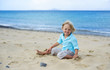 Cute little smiling boy plays on the beach
