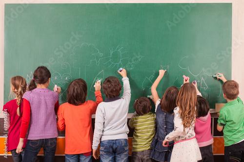 Fotografía  Grupo de nueve niños de dibujo en la pizarra de la escuela con tizas