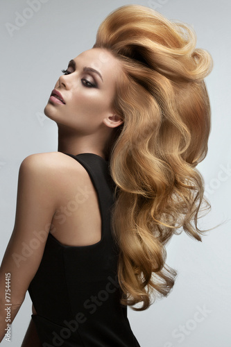 Stampa su Tela  Hair volume.  Portrait of beautiful Blonde with Long Wavy Hair.