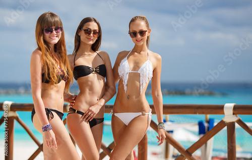 Obraz Beautiful girls in bikini relax poolside at the ocean background - fototapety do salonu