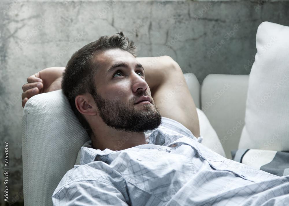 Fototapeta Attraktiver Mann mit Bart entspannt auf der Couch