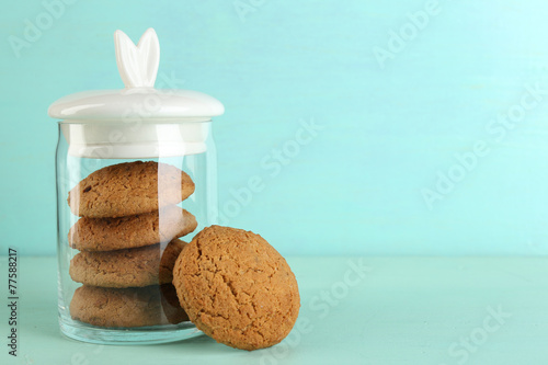 Foto Tasty cookies in glass jar on color wooden background