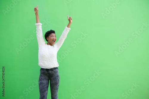 Happy african american woman cheering with arms raised