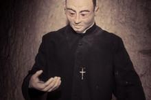 Close Up Priest Statue In Blac...