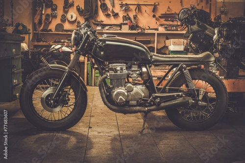 Tuinposter Fiets Vintage style cafe-racer motorcycle in customs garage