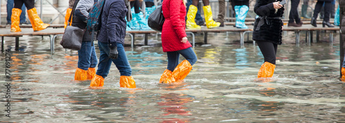 Obraz na plátně Close Up of legs with boots due to the high water in Venice.