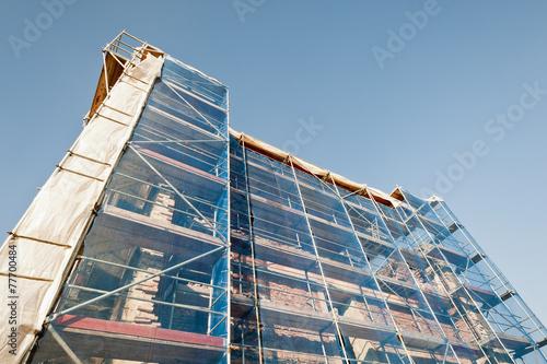Poster London Ein Baugerüst mit Sichtschutz umspannt eine Bauruine