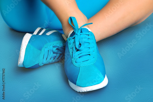 Fotografía  Female feet in turquoise sneakers on turquoise sports mat