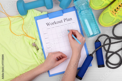 Fototapeta Sports trainer amounts to workout plan close-up