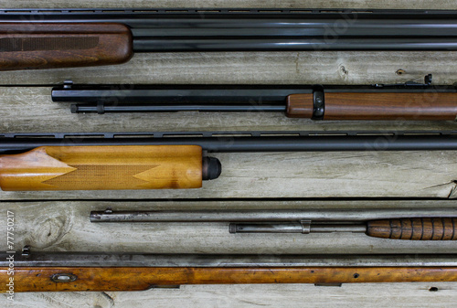 Fotografía  Firearms hanging on rustic wooden background