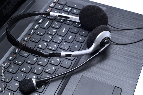 Headset lying on a laptop computer keyboard Fototapet