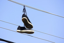 Old Used Sneakers Hanging On W...