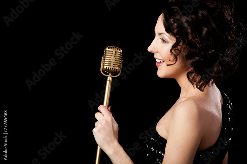 Photo  Beautiful brunette girl vocalist singing with smile holding gold