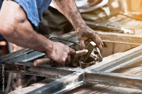 Fotografía  Dirty worker hands doing hammer work on construction site