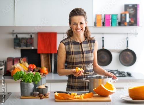 Fototapeta Portrait of happy young housewife cooking pumpkin obraz