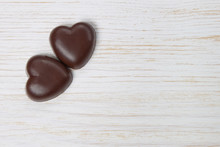 Chocolate Candy Hearts On A Wooden Background