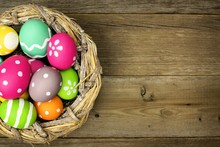 Easter Eggs In A Nest Over Old Wood Background