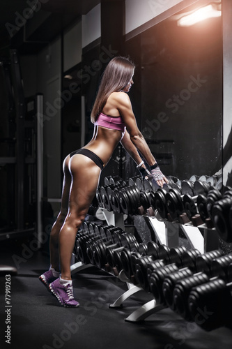 Sexy athlete with a dumbbell in the gym lean on dumbbell row