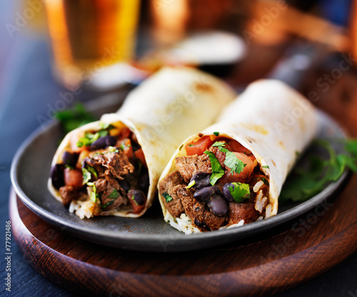 Fotografía  mexican beef burritos with beer in background