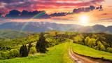Fototapeta Tęcza - road through the meadow on hillside at sunset