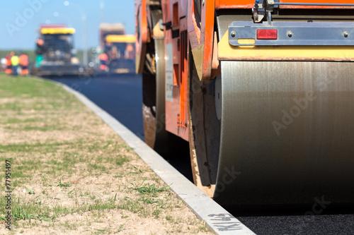Poster Retro Road roller compacting asphalt near curb stone