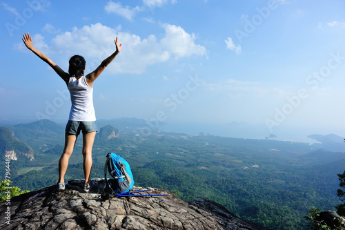 Fotografiet  strong confident woman hiker open arms at on mountain peak rock