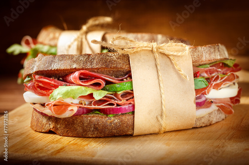 Staande foto Snack Sandwich with bacon and fresh vegetables on vintage wooden cutti