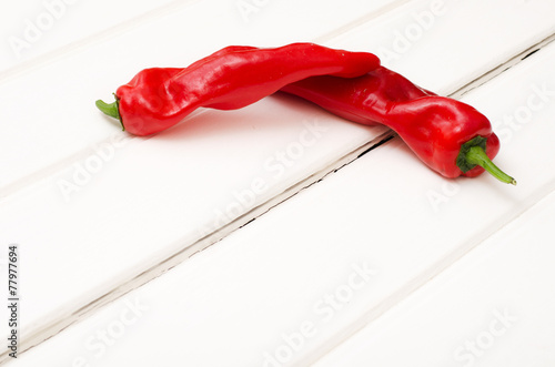 Staande foto Hot chili peppers Two sweet red pepper on white wooden boards