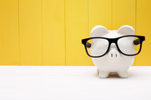 Piggy Bank With Glasses Over Y...