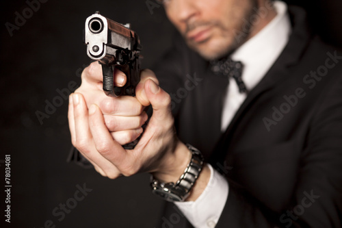Plagát  handsome man in a suit aim with a gun