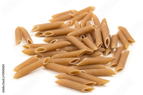 Fotografiet Closeup of pile of uncooked penne rigate pasta, isolated