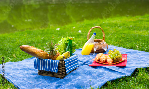 Fotoposter Picknick Picnic basket with fruits, bread and bottle of white wine