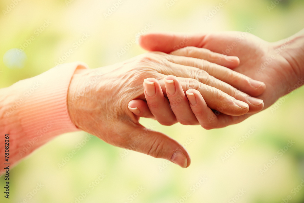 Fototapety, obrazy: Old and young holding hands on light background, closeup