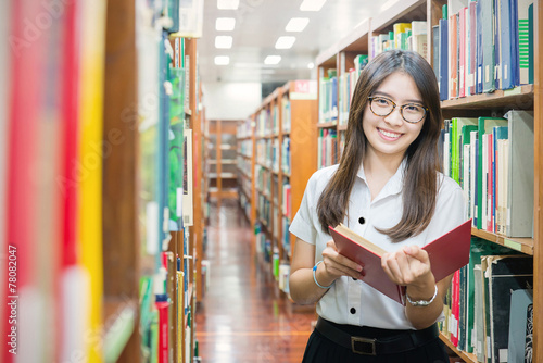 Fotografia  Asian student in uniform reading in the library at university