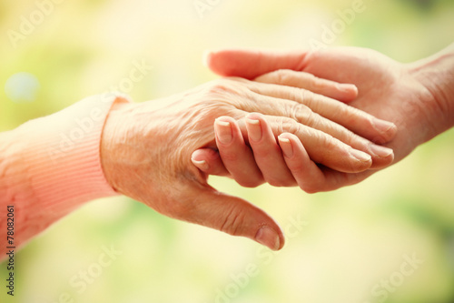Fotografie, Obraz  Old and young holding hands on light background, closeup