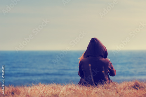 Girl sitting on a meadow with a beautiful sea/ocean view.