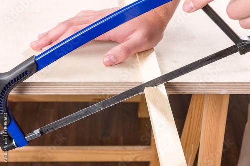 Fotografie, Obraz  Holz wird mit Bügelsäge gesägt