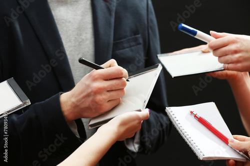 Elegant man signing autograph in notebook on dark background Canvas Print