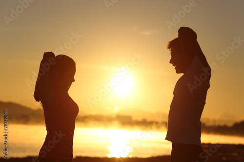 Fotografia  Silhouette of a fitness couple stretching at sunrise